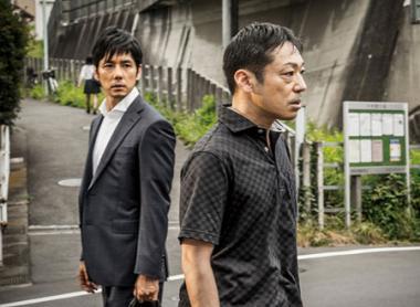 『クリーピー 偽りの隣人』 高倉(西島秀俊)と隣人の西野(香川照之)。後ろには高架線が走っているのが見える。