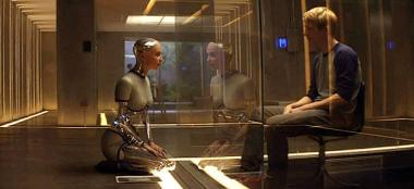 『エクス・マキナ』 エヴァとケイレブはガラスに隔てられながらもテストを行う。
