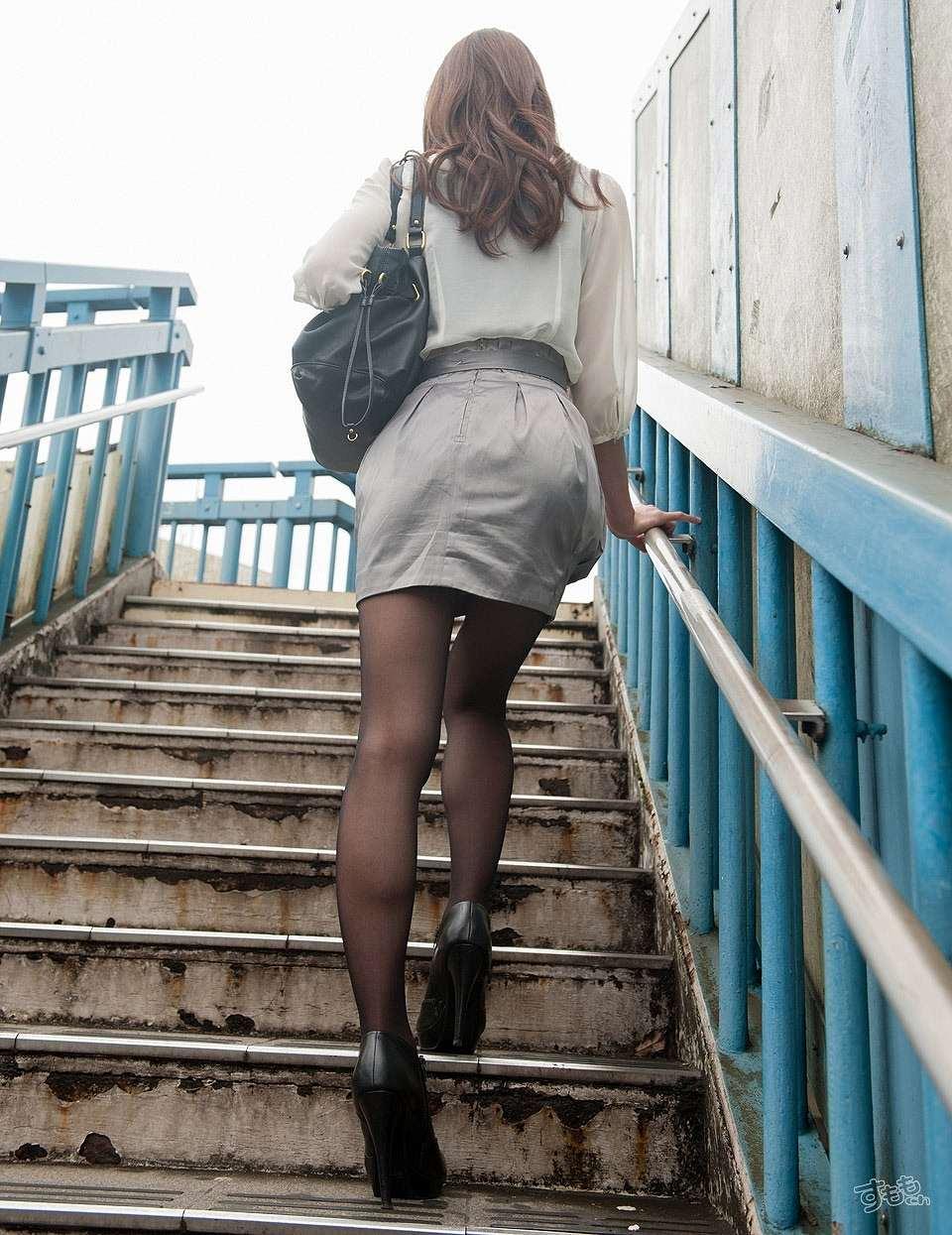 ミニスカートに黒ストッキングで階段を上る女の後ろ姿