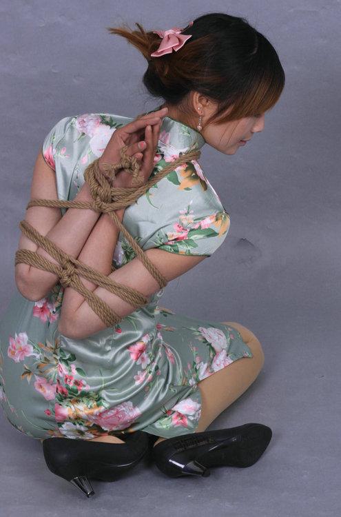 チャイナドレスを着て縛られている女