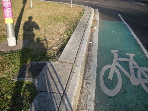 自転車レーンをゆく自分の影を自撮り