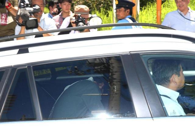 車両の後部座席で顔を伏せて神戸地裁に入る野々村竜太郎被告(手前左)