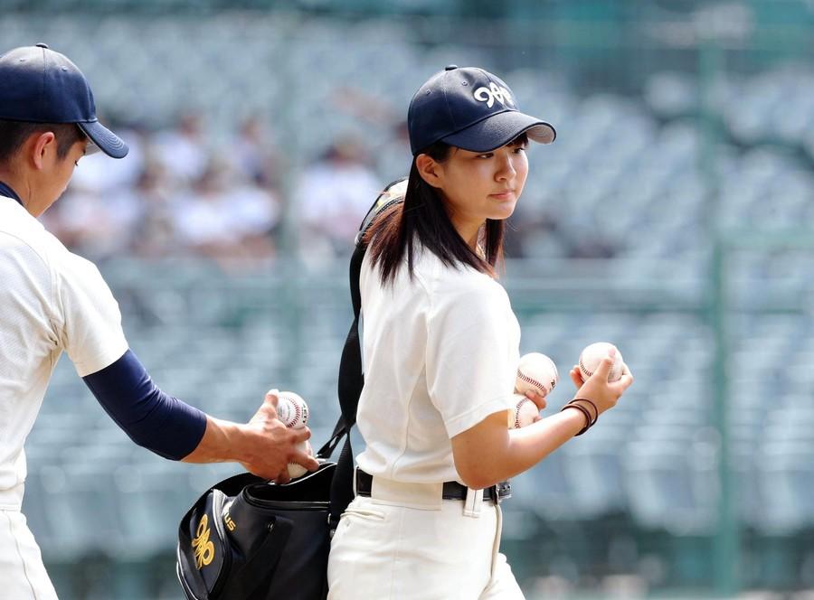 ノッカーに供給するボールをナインから受け取る首藤マネジャー(右)