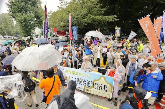 安全保障関連法の成立から丸1年、国会前で行われた大規模抗議集会で登壇し、手を握り合う野党幹部ら