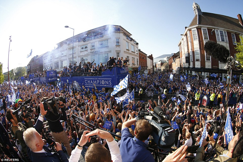 Fans and the media crane their necks to get a better view of the Leicester players as they make their way through the streets