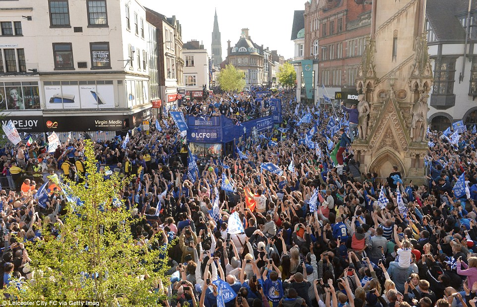 Hundreds of fans lift their mobile phones above their heads to snap a picture of the players bus as it winds through the streets