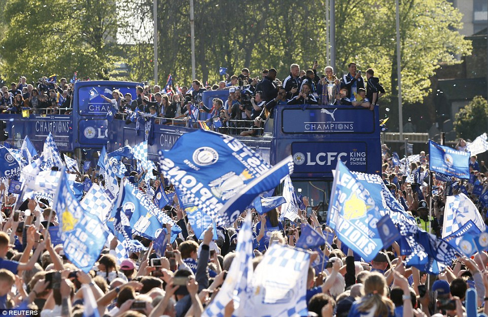 Leicester players and staff parade the Premier League trophy from the top deck of a double-decker bus in the city centre on Monday