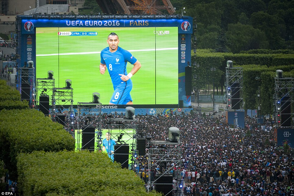 Supporters in the Euro 2016 fan zone at the Eiffel Tower watch the opening game as Payet is pictured on the big screen