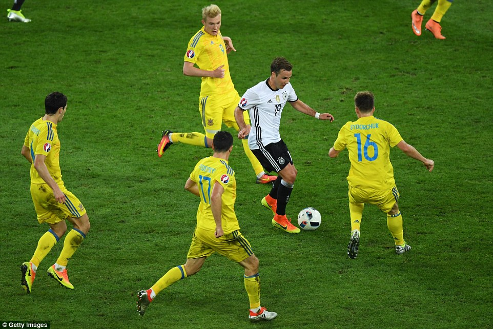 Bayern Munichs Gotze (No 19) tries to escape the challenges of several Ukraine players as he goes on a mazy dribble