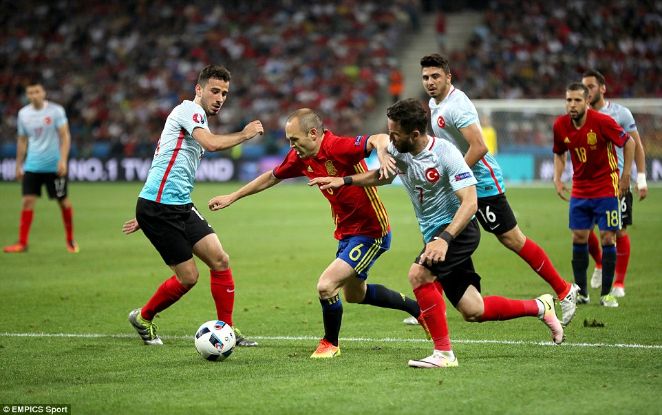 Andres Iniesta (centre) drives forward with the ball under pressure from Turkeys Gokhan Gonul at the end of the fist half
