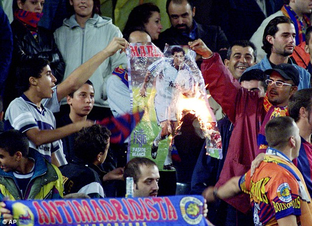 Barcelona fans burn a poster of Figo in the stands during a clash with Real Madrid