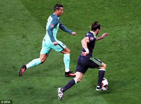 Cristiano Ronaldo (left) of Portugal chases down Real Madrid team-mate and Wales Gareth Bale