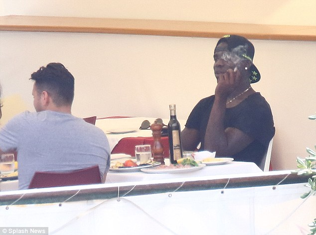 Liverpool striker Mario Balotelli smokes while enjoying the company of friends in Portofino