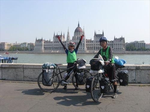 ②ハンガリー、ブダペスト到着:ドナウ川の畔に建つ国会議事堂をバックにして_R