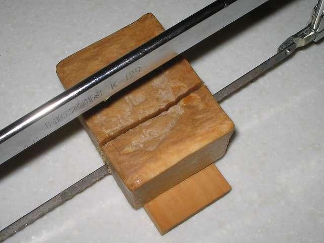 ホーザン K-129 金切りノコを使ってアレッポの石けんをカット中、電子レンジでしっかり加熱していれば金切りノコを両手(持ち手とフレーム部分を握って)でゆっくり押し下げることで簡単にカット可能(加熱が不十分だったりすると石けんが割れる可能性あり)