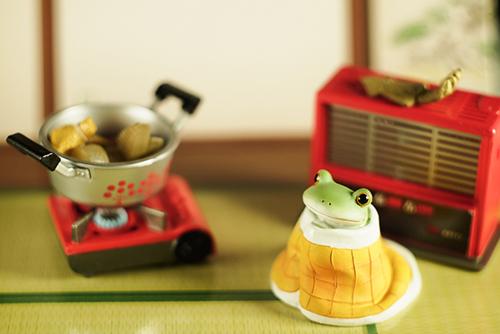 ツバキアキラが撮ったカエルのコポー。冬、寒いので、布団にくるまって、ストーブの前で、おでんが煮えるのを待っているコポタロウ。
